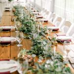 a long head table for a wedding reception is set with fresh greenery, burgundy napkins, and crate and barrel china with water goblets.